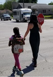 Brittany walks a student across the street after school.